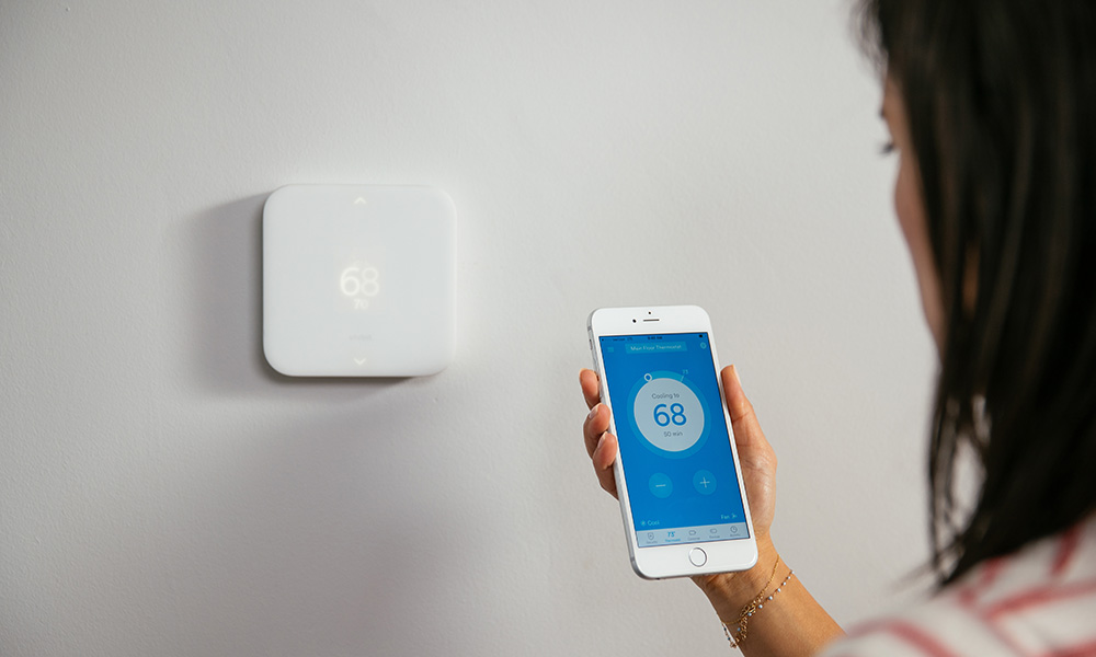 A woman uses the Vivint Smart Home app to control her Element Thermostat