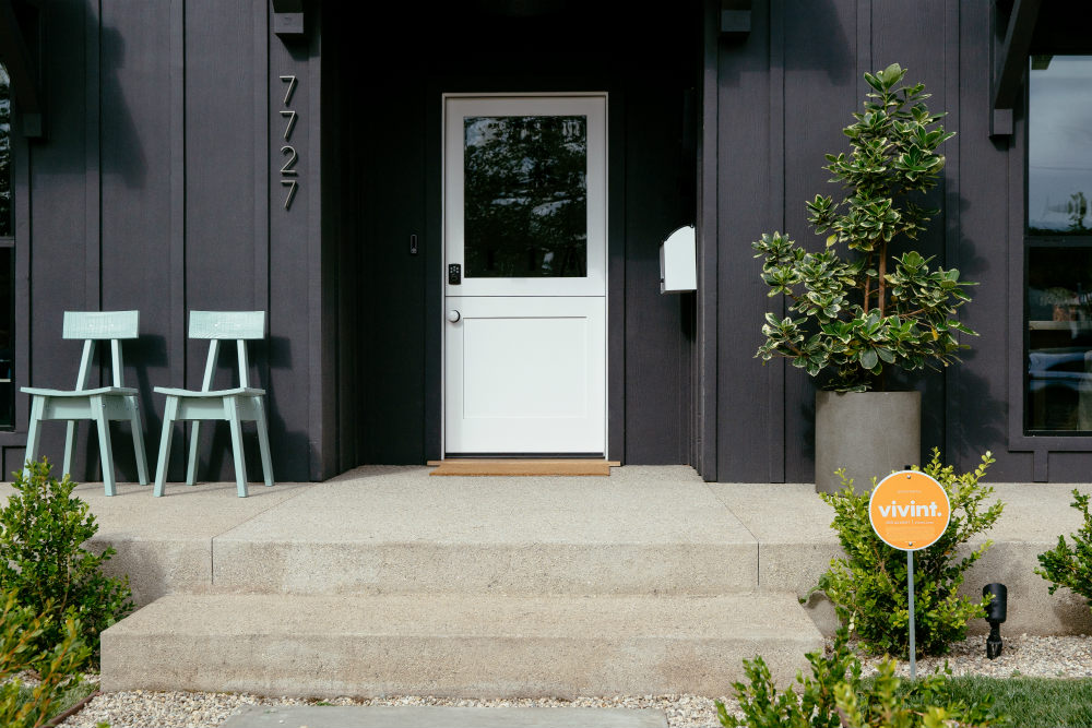 Vivint protected home with a sign in the yard and a smart lock at the door