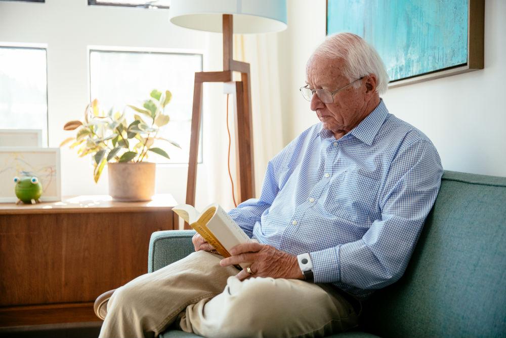 Elderly man with a Vivint panic pendant reading a book