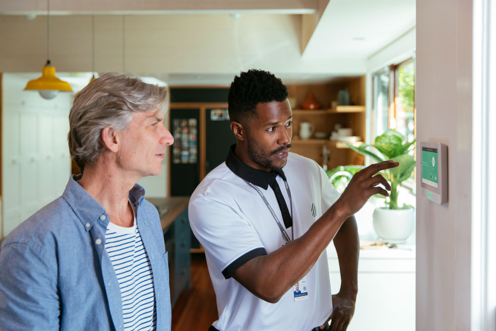 Vivint professional showing a man how to use the Vivint Smart Hub
