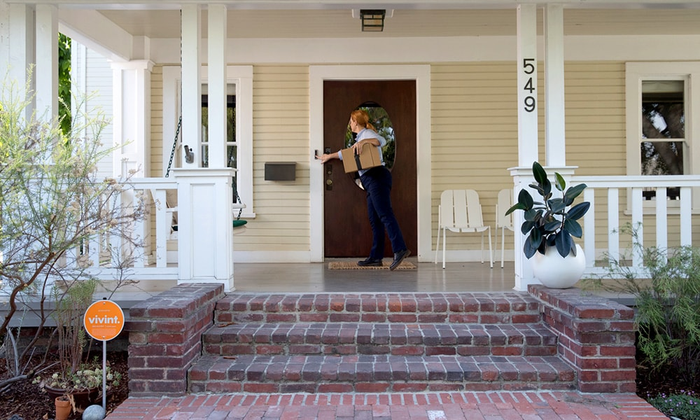 A delivery person rings a Vivint Doorbell Camera