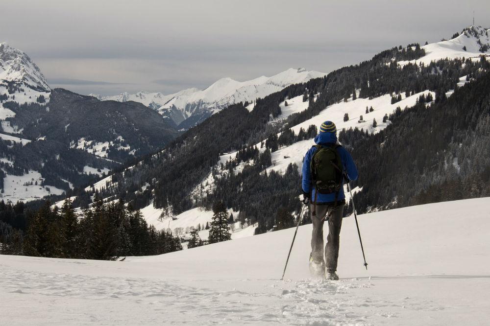 man snowshoeing mountains