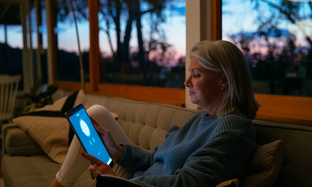 A woman monitors her smart thermostat from a tablet
