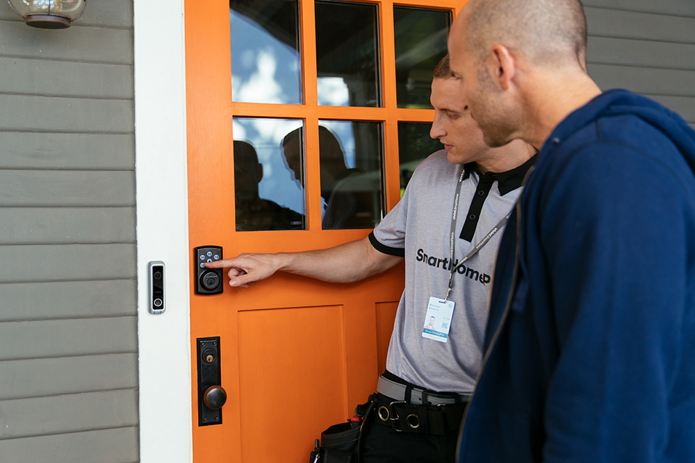 Vivint professional teaching man how to use the Vivint Smart Lock and Doorbell camera