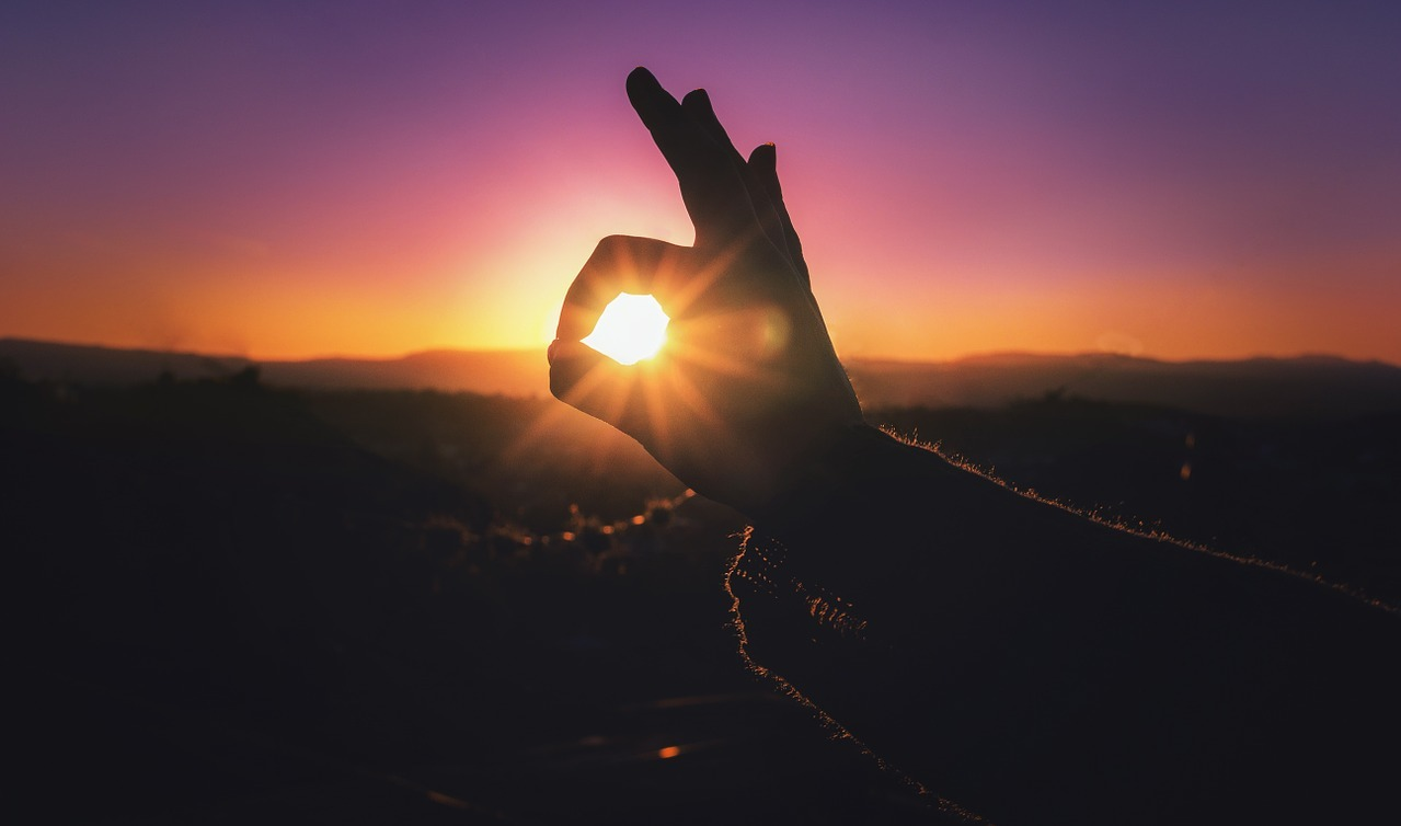 Hand In Front Of Sunset Background